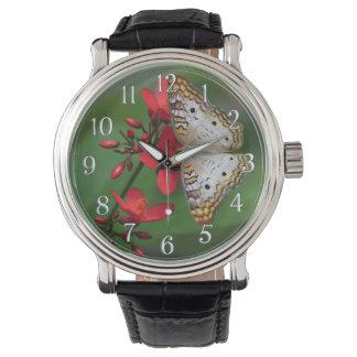 Mariposa blanca en la fotografía roja de las reloj de mano
