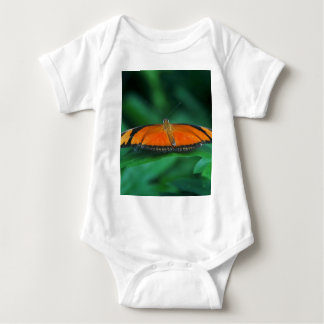 Mariposa brillante del naranja y del negro en la mameluco de bebé