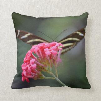 mariposa de la cebra detrás de la flor rosada de l almohada