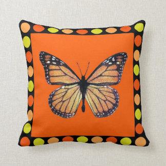 Mariposa de monarca bonita en el naranja con los l almohadas