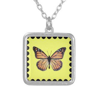 Mariposa de monarca bonita en el oro colgante cuadrado