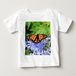 Mariposa de monarca en jardín polera