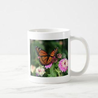 Mariposa de monarca en la flor del Lantana Taza