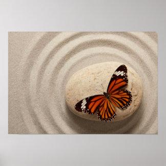 Mariposa de monarca en una piedra en un jardín del póster