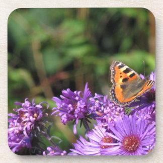 Mariposa de monarca y flores púrpuras posavasos de bebida