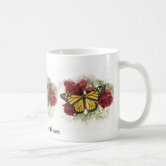 Mariposa de monarca y taza de los rosas rojos