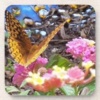 Mariposa de oro, flores rosadas y diseño de la posavasos