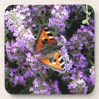 Mariposa de pavo real anaranjada en las flores púr posavasos