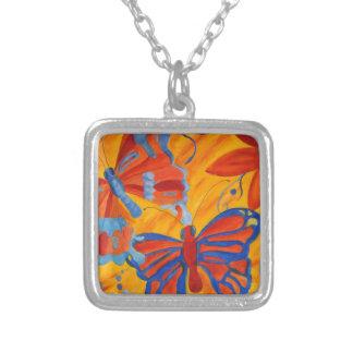 Mariposa del naranja, azul y roja colgante cuadrado