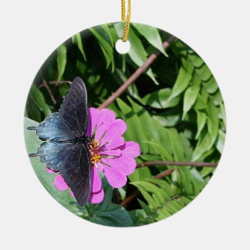 Mariposa del negro azul en la flor púrpura, hoja v ornamento para arbol de navidad