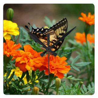 Mariposa en el reloj de pared anaranjado y amarill