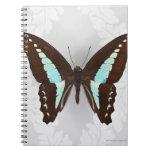 Mariposa en fondo del papel pintado libro de apuntes con espiral