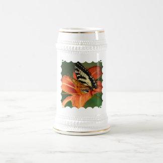 Mariposa en la cerveza Stein del lirio Taza