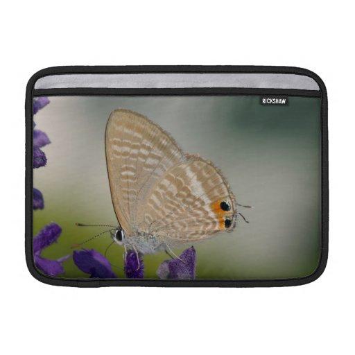Mariposa en la flor púrpura fundas MacBook