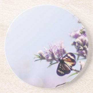 Mariposa en rama púrpura del flor posavasos para bebidas
