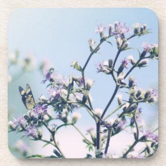Mariposa en rama púrpura del flor posavasos de bebidas