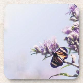 Mariposa en rama púrpura del flor posavasos de bebida