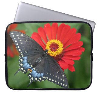 Mariposa negra en la manga roja del ordenador manga portátil