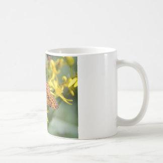 Mariposa negra y anaranjada en las flores taza de café