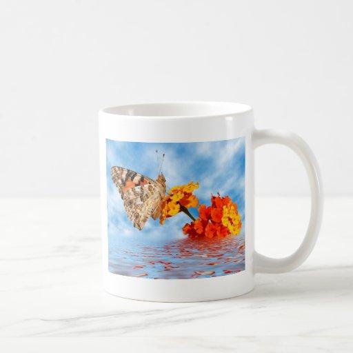 Mariposa pintada de la señora en la flor taza de café