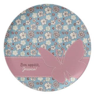 Mariposa rosada en modelo azul floral del vintage platos