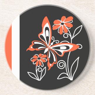 Mariposa y flores anaranjadas llamativas en negro posavasos de arenisca