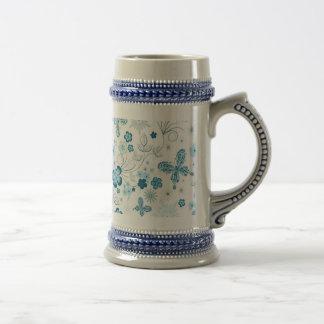 Mariposas azules blancas de las flores de los copo tazas de café