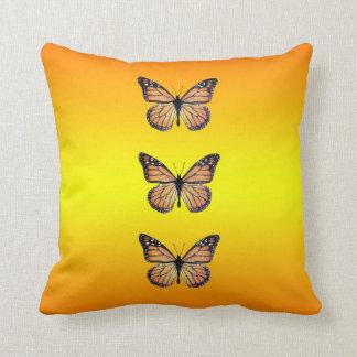 Mariposas de monarca bonitas en el naranja cojin