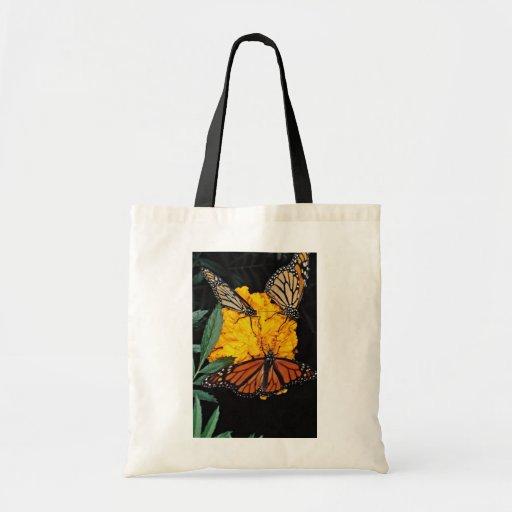 Mariposas de monarca que alimentan las flores bolsas de mano