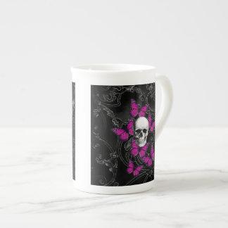 Mariposas del cráneo y de las rosas fuertes de la taza de porcelana
