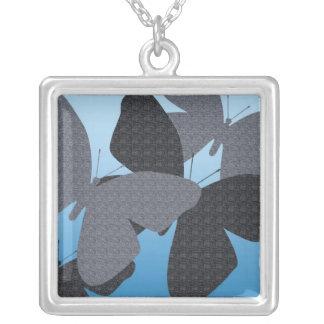 Mariposas negras y grises en el collar azul