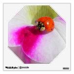 Mariquita en la etiqueta de la pared de la petunia