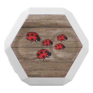 Mariquitas en el tablero de madera altavoces bluetooth blancos boombot REX