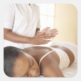 Masaje trasero. Mujer que recibe un masaje trasero Pegatina Cuadrada