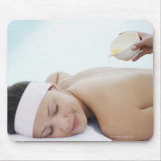 Massage oil being poured on womans back mouse pad