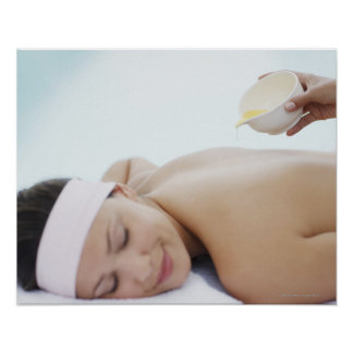 Massage oil being poured on womans back poster