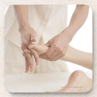 Massage therapist applying foot massage 2 beverage coaster