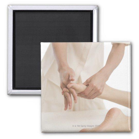 Massage therapist applying foot massage 2 magnet