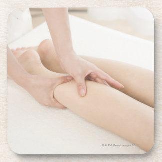 Massage therapist applying foot massage coasters