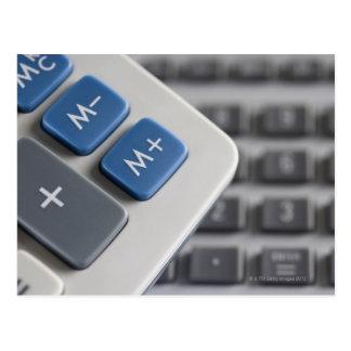 Mathematical symbols on a calculator and a postcard