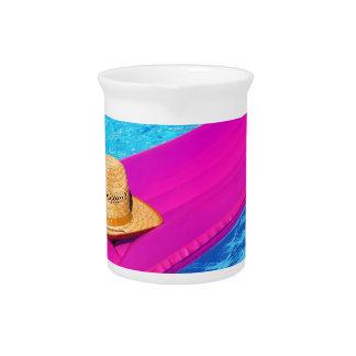 Mattrass rosados del aire con el gorra en piscina jarra de beber