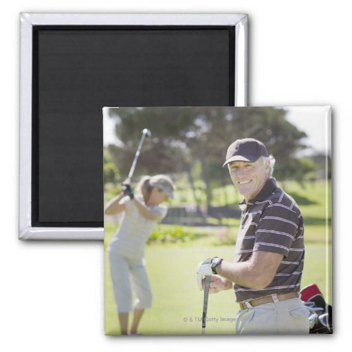 Mature couple playing golf magnets