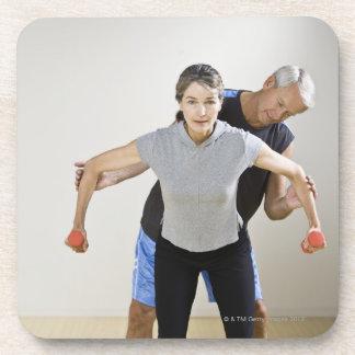 Mature man assisting woman, exercising using drink coaster