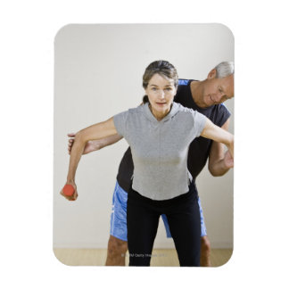 Mature man assisting woman, exercising using magnet