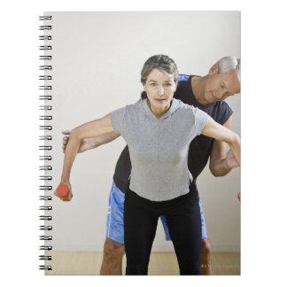 Mature man assisting woman, exercising using notebook