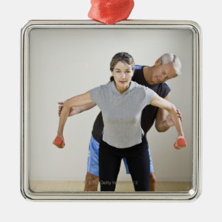 Mature man assisting woman, exercising using square metal christmas ornament