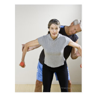 Mature man assisting woman, exercising using postcard