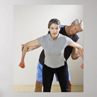 Mature man assisting woman, exercising using posters