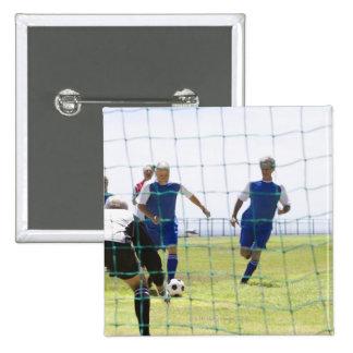mature men kicking soccer ball towards pinback button