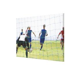 mature men kicking soccer ball towards canvas print